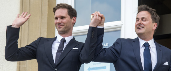 Luxembourg's Prime Minister Xavier Bettel, right, holds up the hand of his partner Gauthier Destenay, with a wedding band on his finger, as they leave the town hall after their marriage in Luxembourg, on Friday, May 15, 2015. The marriage comes one year after the parliament approved legislation to turn Luxembourg into an increasing number of countries allowing same-sex marriages. Bettel and Destenay have been civil partners since 2010. (AP Photo/Charles Caratini)
